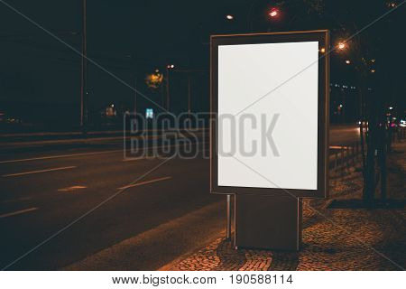 Empty information placeholder near night city highway blank vertical poster on paving stone next to road white mock-up of billboard with copy space place for text your logo or advertising