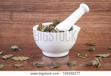 Dried lemon balm in white mortar on rustic board healthy lifestyle herbalism alternative medicine