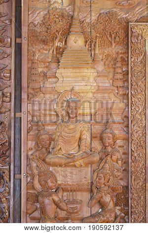 A wooden carving of seated buddha and temple, Thailand