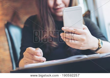 A beautiful Asian woman holding and using smart phone with magazines on wooden table in the bistro cafe