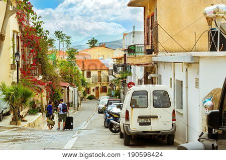 Rethymno Greece - May 3 2016: Cars parked on narrow cobbled street. Tourists walk on city touristic trails. Resort classic Greek architecture in port city Rethymno Crete Greece