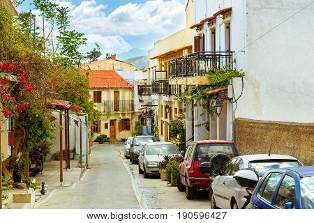 Rethymno Greece - May 3 2016: Cars parked on narrow cobbled street. Walk on city touristic trails. Resort classic Greek architecture in port city Rethymno Crete Greece