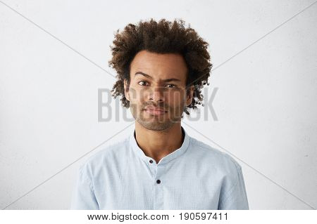 Portrait Of Displeased Mixed Race Attractive Man With Dark Narrow Eyes And Curly Thick Hair Wearing
