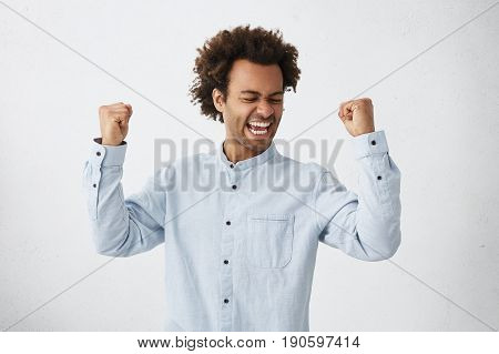 Excited African Male Winner Raising His Fists With Great Happiness Having Good Mood After Winning Ga