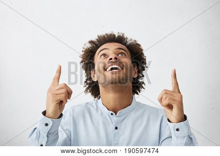 Indoor Shot Of Elegant Happy Male With African Hairstyle Looking Up Raising Index Fingers Isolated O