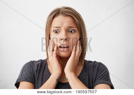 Close-up Portrait Of Puzzled Woman With Dark Bugged Eyes Holding Hands On Cheeks Looking Desperately