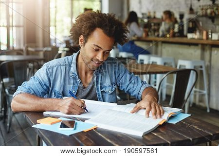 Stylish Hipster Guy With African Hairstyle Wearing Denim Shirt Sitting In Cafeteria Working With Boo