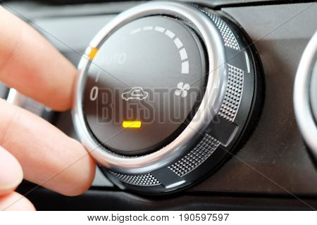 hand on air positioner control air flow switching in car, air conditioner control panel.
