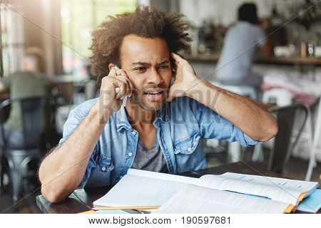 Hnadsome Dark-skinned College Student Dressed Casually Looking Frustrated, Plugging One Ear While Tr