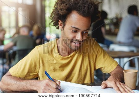 Focused Student Male With Dark Bushy Hair And Bristle Wearing Casual T-shirt Writing Something In Hi