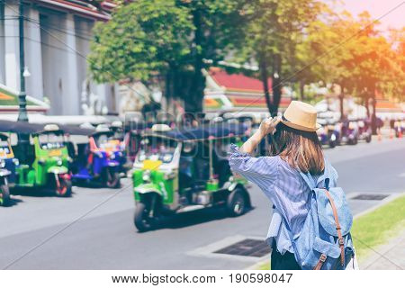 Young woman traveler with sky blue backpack and hat looking the way with tuk tuk thailand background from wat pho at Bangkok Thailand. Traveling in Bangkok Thailand