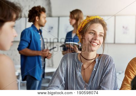 Smiling business lady wearing trendy shirt and yellow head bandage having pleasant smile while having business meeting with her partners isolated over working space. Communication work concept