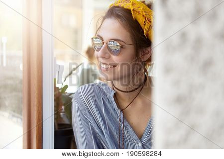 Portrait Of Pretty European Woman In Sunglasses And Yellow Headband Looking Outside From Building En