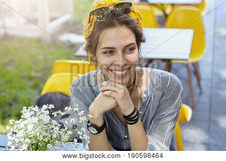 Smiling Charming Woman With Sunglasses On Head Dressed Casually Having Rest While Sitting Outdoors A