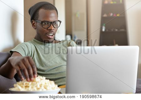 Headshot Of Dark-skinned Hipster Male In Big Shades Sitting At Home Watching His Favourite Serial Ea