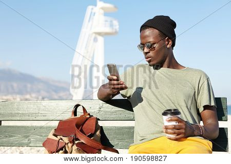 Young Attractive Dark-skinned Male Wearing Black Hat, Casual T-shirt And Yellow Trousers Sitting At