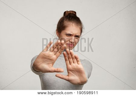 Body Language. Disgusted Stressed Out Angry Beautiful Young Woman With Hair Knot Posing At Studio Wa