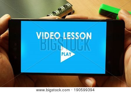 Hands holding phone with Video lesson. Online education concept.