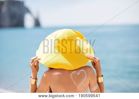 Back view on the woman in yellow hat standing on the beach on the blue water backround