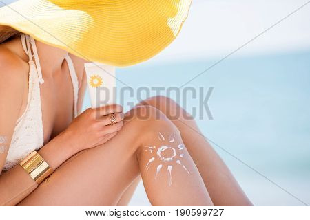 Beautiful woman in yellow hat sunbathing holding a bottle with sunscreen UV protective lotion on the beach
