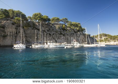 CASSIS,FRANCE-AUGUST 10,2016:The port inside a creek near Cassisa French village with colorful boats moored and the lighthouse during a summer day.