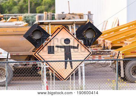 Faded orange signs near trucks parked in a road maintenance yard.