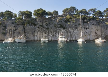 CASSIS,FRANCE-AUGUST 10,2016:Moored boats inside a creek near Cassisa French village with colorful boats moored and the lighthouse during a summer day.