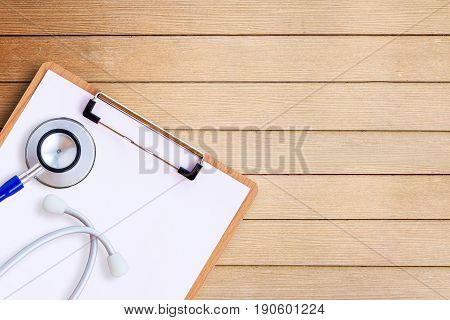 Medical equipment with medical form on wooden doctor desk background horizontal medical concept. top view with copy space for any design health concept