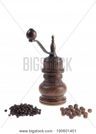 Mill for pepper with black peppercorns and allspice corns isolated on white background
