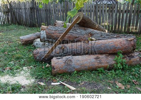 Old axe standing against a piled pieces of firewood. Axe stuck in a stump
