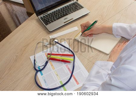 Medicine doctor's working table. Healthcare and medical concept. Doctor sits in a medical office in the clinic and writes medical history