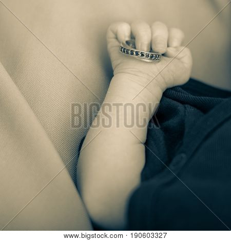 Newborn holding a wedding ring. Closeup of tiny hand.