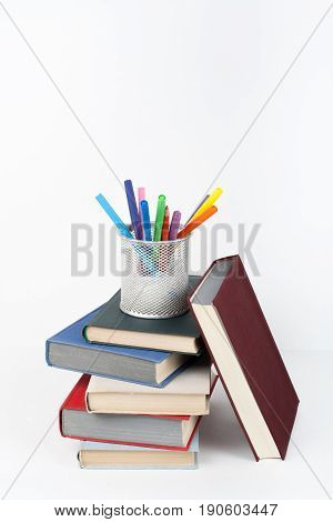 Open book, hardback colorful books on wooden table, white background. Back to school. Pens, pencils, cup. Copy space for text. Education business concept