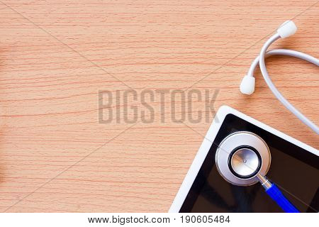 Workplace of a doctor. Stethoscope and smart phone on wooden desk background. Top view with copy space. Healty concept.