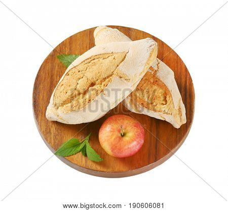 two diamond shaped rustic bread rolls and fresh apple on round wooden cutting board