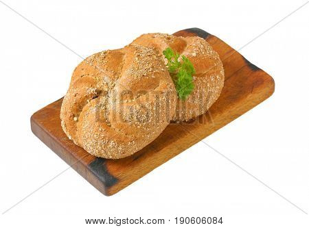 two whole wheat buns on wooden cutting board