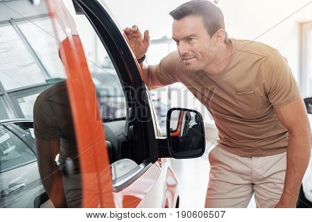 How it looks inside. Beaming adult man viewing passenger compartment while standing near car in salon