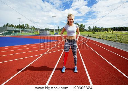 Full length portrait of sporty young female standing with hands on hips on running tracks