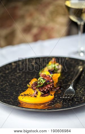 Tentacles of an octopus on a mango puree restaurant serving of a dish. Restaurant food concept.