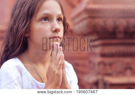 Portrait of praying little girl in church