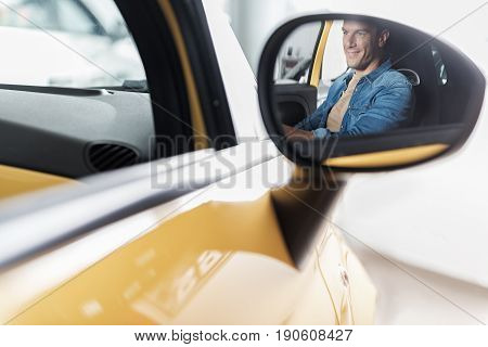 Man demonstrating happiness while reflecting in close up wing mirror of vehicle in car dealership