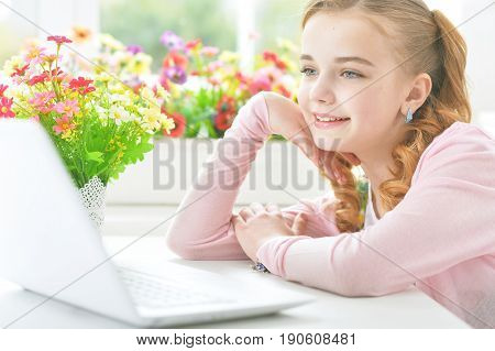 Pretty little girl sitting at table with modern laptop