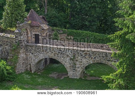 The photo shows a stone bridge forming part of Czocha castle located in the village of Leśna in south-western Poland. The bridge is supported by arched bays. On the left at the end of the bridge you can see the guardhouse.