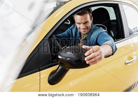 Man showing cheerfulness while regulating looking glass. He sitting in modern automobile