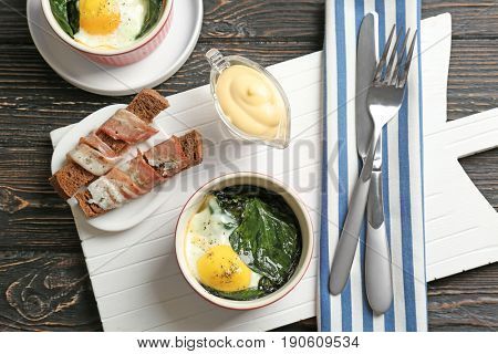 Delicious eggs Florentine in bowl on white wooden board