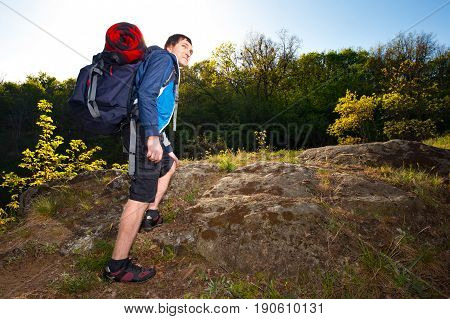 A young man backpackers hiking on the path during summer. Travel hiking backpacking tourism and people concept