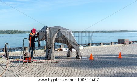 Samara, Russia - June 2017 - Welder on the street makes an elephant of the iron city concept on the embankment of the river Volga, Samara.