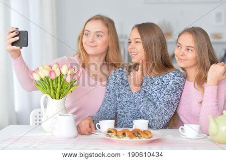 Portrait of three teenage girls making selfie