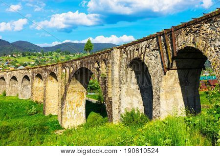 Scenic summer view of the ancient abandoned railway arch bridge viaduct and Carpathian Mountains in Vorokhta, Ivano-Frankivsk Region, Ukraine