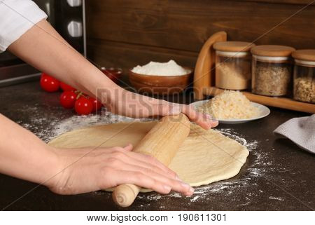 Female hands rolling out dough for pizza on table